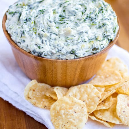 Spinach and artichoke dip in a wood bowl with chips surrounding it.