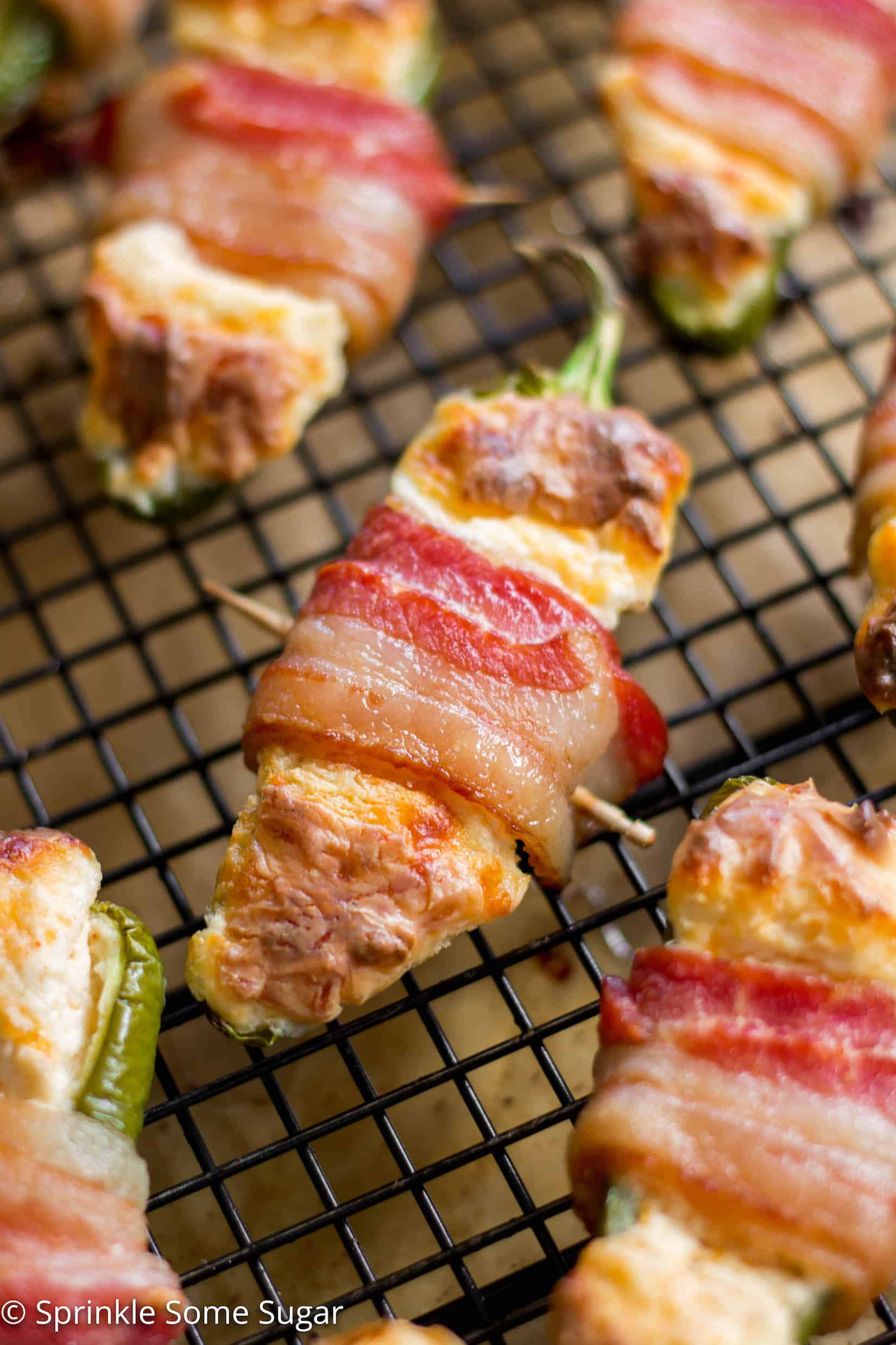 Bacon-Wrapped Jalapeño Poppers - Creamy, cheesy filled jalapeños are wrapped in a layer of juicy, crispy bacon. Talk about mouth-watering!