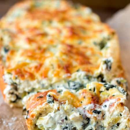 Crispy, crusty french bread gets filled with an extra creamy spinach and artichoke dip. - Spinach and Artichoke Stuffed Bread
