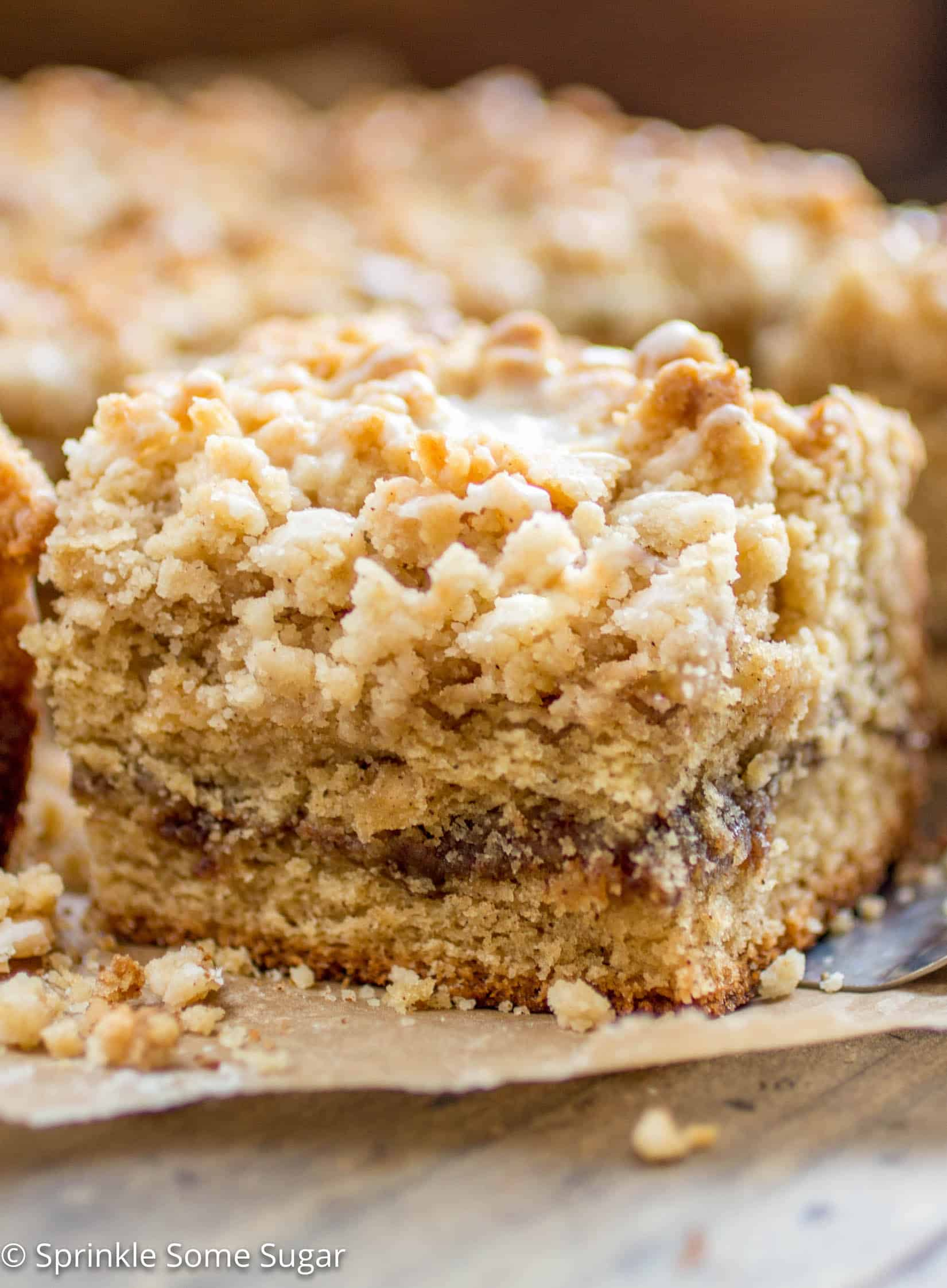 Cinnamon Swirl Coffee Cake - Soft lightly spiced coffee cake is filled with a gooey cinnamon swirl center and topped with a sweet streusel topping + vanilla glaze!