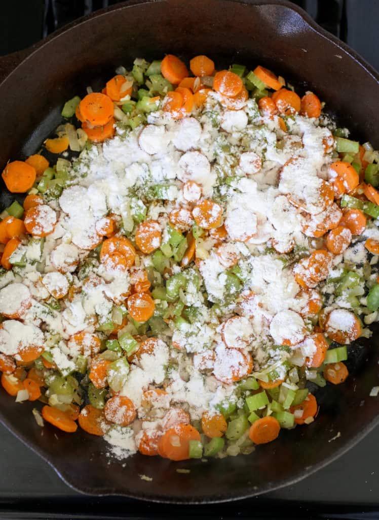 Flour sprinkled on top of sautéed carrots, celery and onion.