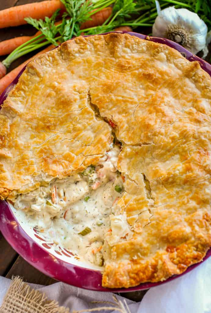 Whole chicken pot pie with slice missing.