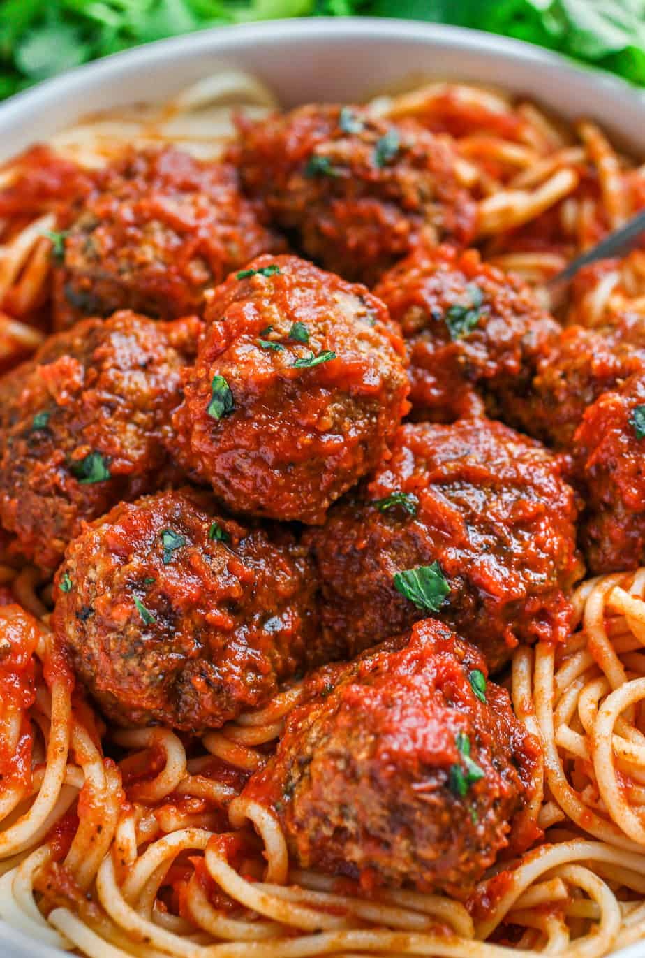 Meatballs in sauce on a bed of spaghetti.